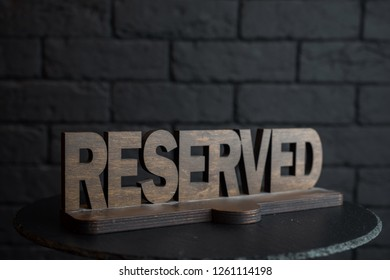 """Vintage wooden carved figure """"Reserved"""" on an empty black table in a restaurant against a black brick wall. Exclusive decorative plate """"Reserved"""". Table for VIP guests."""