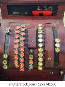 A vintage wooden cash register or till showing pre decimal currency £ S d. The currency buttons are coloured red, yellow, blue and black and an arrow points to the sum. A base drawer holds the cash.