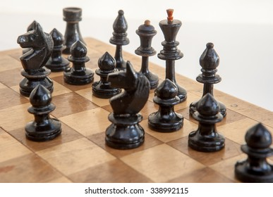 Vintage wooden chess on a wooden chess board. Black chess pieces.