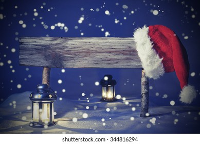 Vintage Wooden Christmas Sign And Santa Hat With White Snow In Snowy Scenery. Copy Space Free Text For Advertisement. Blue Silent Night With Snowflakes. Lantern And Candlelight