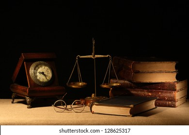 Vintage wooden clock near brass weight scale and books on dark background