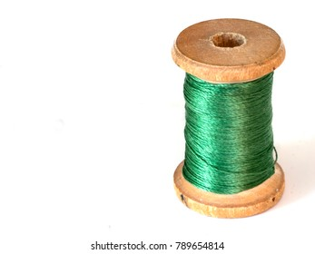 Vintage wooden coil with green silk threads on white background