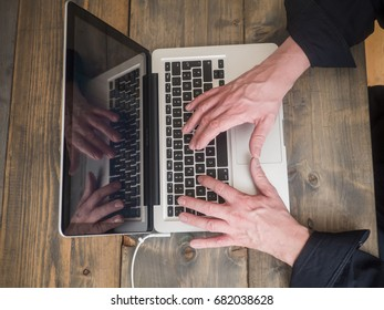 Vintage wooden desktop top view, male hands typing on a laptop.High Angle View.