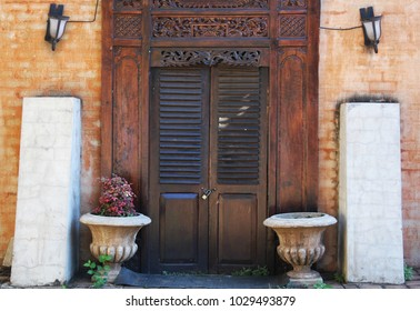 Vintage wooden doors with lock and flower pots