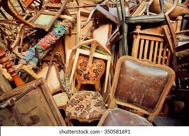 Vintage wooden furniture in trash warehouse of antique market. Retro background