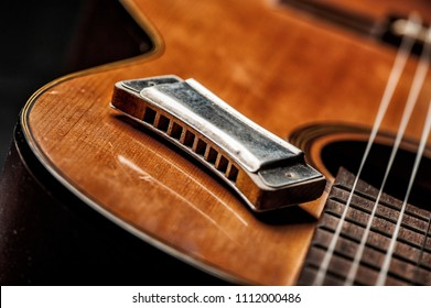 vintage wooden harmonica lying on an old acoustic guitar.