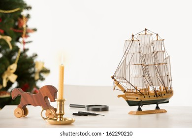 Vintage Wooden Horse and Ship on Santa's work table, Christmas Tree on background