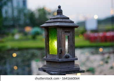 Vintage wooden lamp in the green garden.