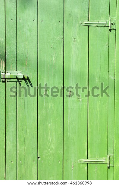 A vintage wooden locked door painted green color with metal hinges, daylight, vertical plank
