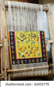 vintage wooden loom with half knit colored carpet on threads