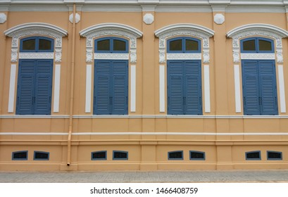 Vintage wooden louver windows and fixed glass windows on wooden frame with concrete walls background. Ventilation and lighting design concept.