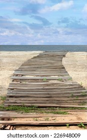 Vintage Wooden Plank Path on Sandy Beach Heading to Sea with vertical orientation
