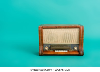 vintage wooden radio receiver on turquoise background