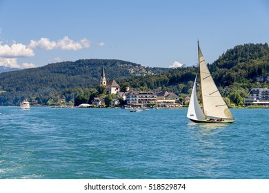 Vintage wooden sailboat  sailing on Worthersee lake, Carinthia, Austria. Maria Worth with church in background.