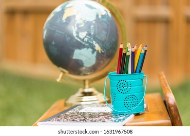 Vintage wooden school desk with colored pencils, globe and school supplies