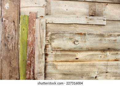 Vintage Wooden Scrap Plank Fence background weathered by sea air. Asymmetrical pattern composition with a green board.