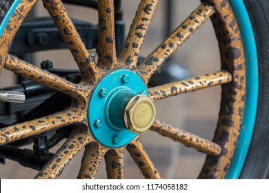 Vintage wooden spoke car wheel. Close-up of wood spokes on a classic motor vehicle. History of automobiles.