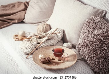 Vintage wooden spokes and yarn on a cozy sofa with a sweater and a Cup of tea . Still life photo. The concept of comfort