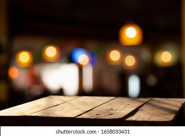 Vintage wooden table on blurred golden bokeh on a dark background. Cafe-dining-restaurant.
