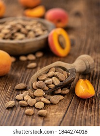 Vintage wooden table with a portion of shelled Apricot Kernels (close up shot; selective focus)