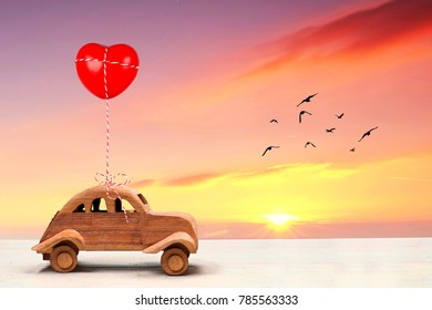 vintage wooden toy car with red heart at sunset with birds