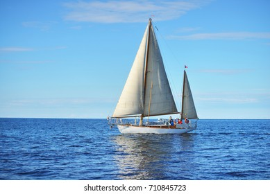 Vintage wooden two mast yacht sailing in a open sea on a clear day
