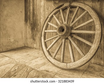 Vintage wooden wagon wheel with spokes, axle, and an iron rim,  in tones of black, white, and gray/grey.