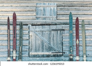 Vintage wooden weathered ski's in front of an old barn with snowfall
