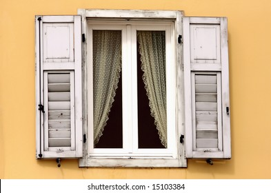 Vintage wooden window with lace curtain