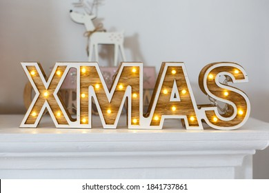 """Vintage wooden word """"Xmas"""" with lights on the shelf. New year decorations in rustic style. Wooden letter on white background. Lantern in view of the word """"XMAS"""", classic Christmas decore"""