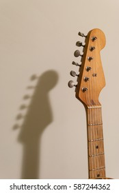 Vintage worn electric guitar head and neck close up with retro tuners, isolated on beige background, with it's shadow on the wall
