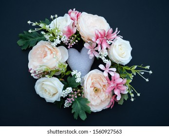 Vintage wreath of spring summer flowers   with a grey heart in the middle on a dark background. Romantic bridal wedding theme.