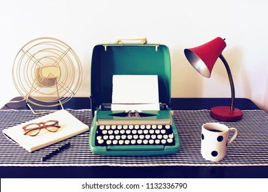 Vintage writers desk with retro aqua coloured typewriter, coffee, and vintage lamp. Journalist workspace from the past that conveys a nostalgic mood.