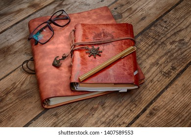 Vintage writing materials still life: two brown leather vintage notebooks or books, glasses and vintage metall brass pen on old antique wooden table or floor. HDR image