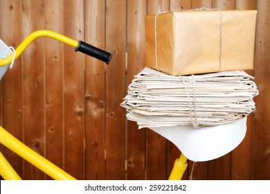 Vintage yellow bicycle with newspaper and parcel, on wooden wall background