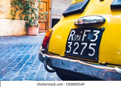 Vintage yellow car in the street with an old car plate in Rome.