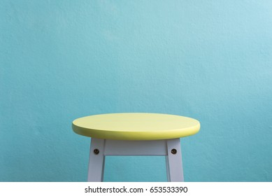 vintage yellow chair on green stone wall background