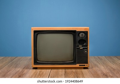 Vintage yellow old TV on wooden table in the room with blue background