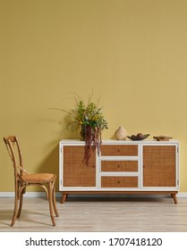 Vintage yellow room with wicket white cabinet, chair, lamp and coffee table.