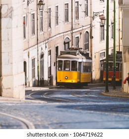 Vintage yellow tramway in Lisbon, Portugal. Bright tram on neutral background building. Tram edit up