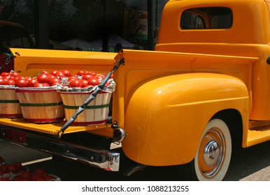 Vintage Yellow Truck with baskets of bright red tomatoes