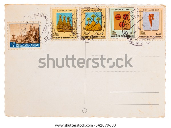Vintage yellowed postcard with post meter stamps and different old stamps from San Marino isolated on white