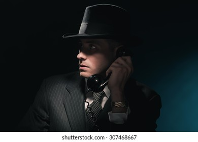 Vintage young detective on the phone with hat in suit and tie. Dark blue background.
