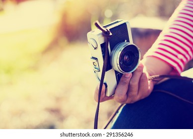 Vintage young hipster girl photographer hand holding retro camera, soft focus