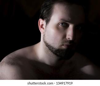 vintage-like low key portrait of young man with beard and hairy shoulders