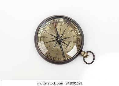 A vintage(old) compass on the glossy table(desk) isolated white at the studio.