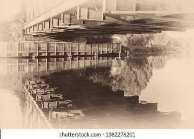Vintage-style photo of reflections in water of the River Cam under the railway bridge in East Chesterton, Cambridge. With wooden walkway into countryside beyond.