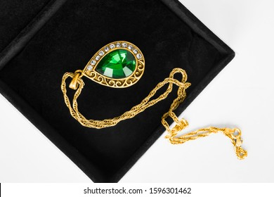 Vintge gold emerald pendant with diamonds in black jewel box closeup