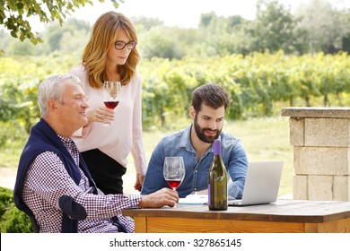 Vintner family working together. Winemaker woman holding a glass of red wine and tasting it. Senior sommelier and young professional man sitting in front of laptop at wine cellar and consulting.