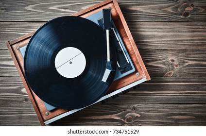 Vinyl player with plates on a wooden table. Entertainment 70s. Listen to music. Top view.